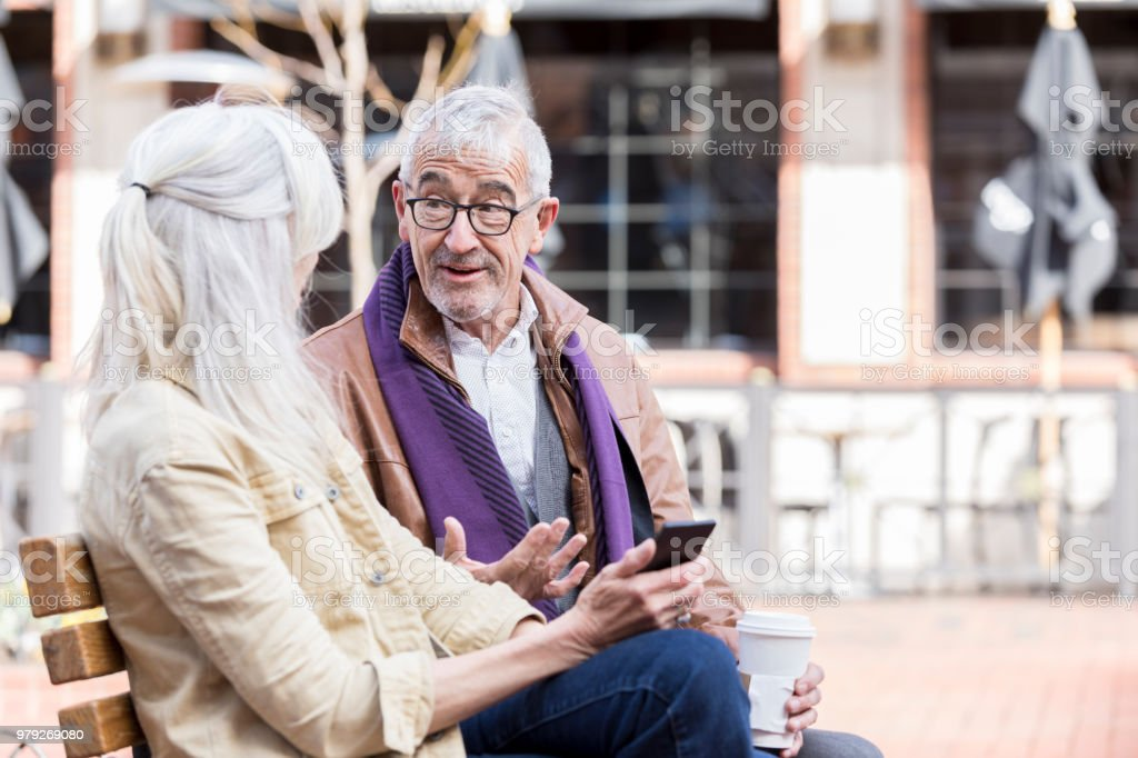 Senior couple have discussion while on park bench stock photo