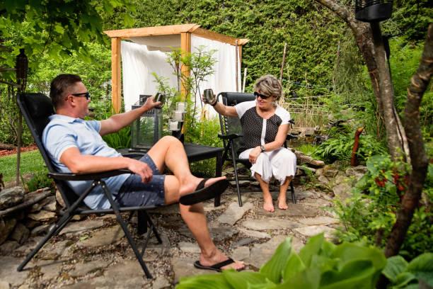 Senior couple having a drink in backyard. stock photo