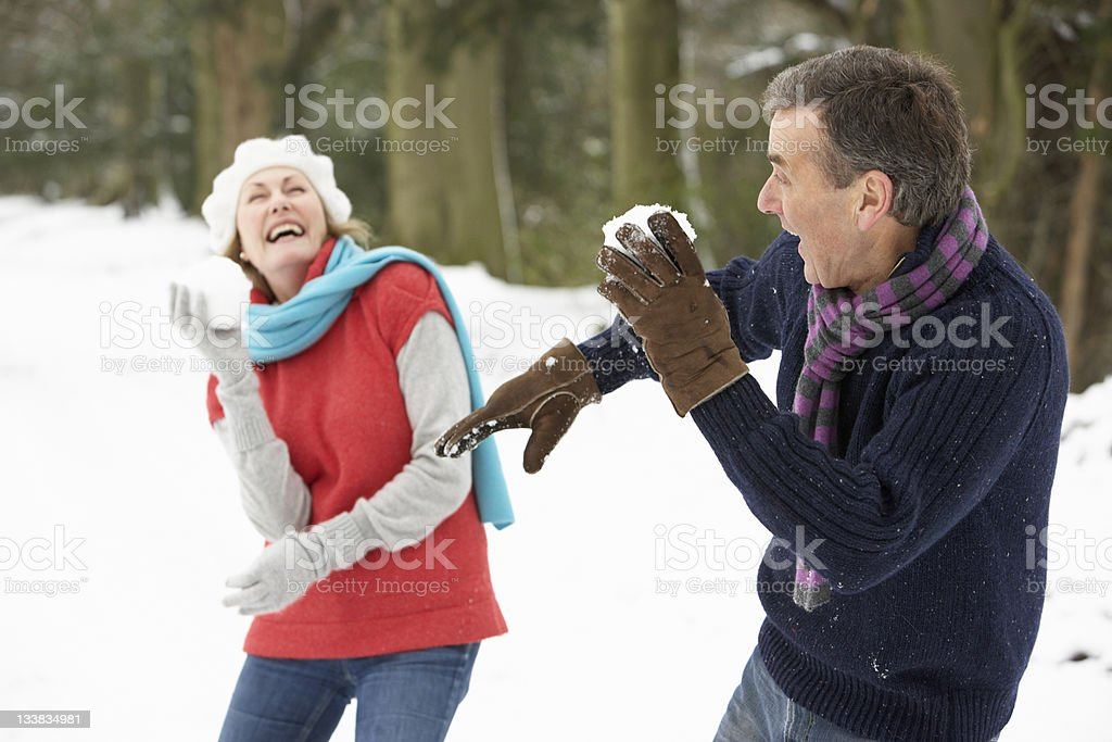 Senior couple having a snowball fight by woodland stock photo