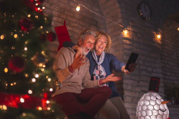 Senior couple having a video call with family on Christmas Eve stock photo