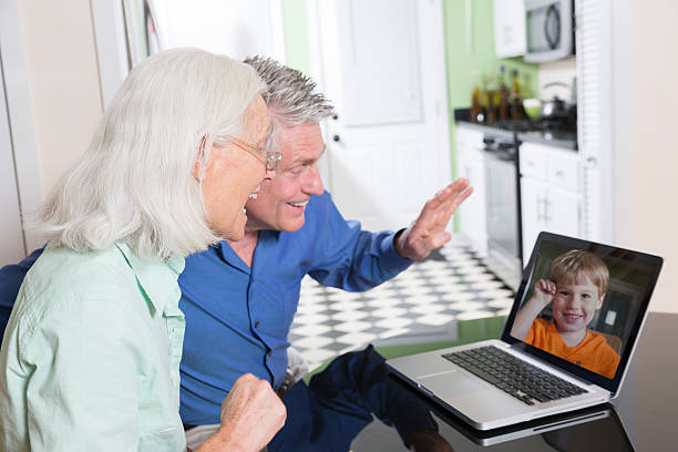 A senior couple having a video chat with their grandson stock photo