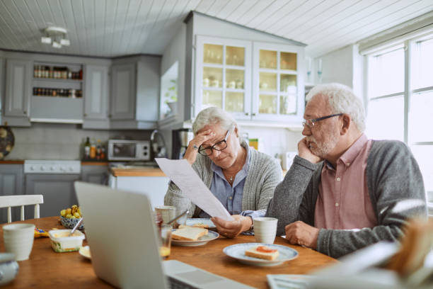 Senior couple having breakfast and doing bills Close up of a senior couple having breakfast and doing bills pension stock pictures, royalty-free photos & images