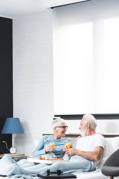 Senior couple having breakfast in bed together stock photo