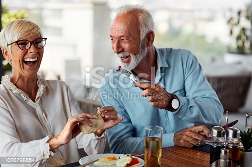 Senior Couple Having Breakfast On The Hotel Rooftop Restaurant. Senior man feeding woman and smiling.