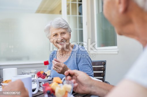Happy senior woman eating fresh fruits during breakfast. Cheerful old lady with grey hair enjoying healthy breakfast with her husband outdoor. Elderly couple in conversation enjoying fresh fruit on the balcony.