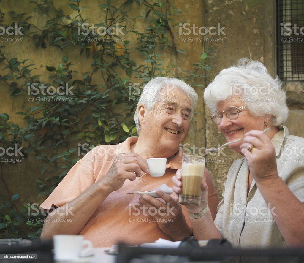 Senior couple having coffee and cappuccino, smiling royalty-free stock photo