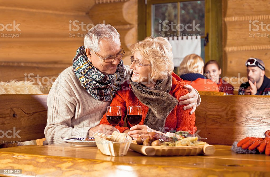 Senior couple having dinner in restaurant after skiing Senior couple wearing winter clothes sitting in a mountain restaurant after skiing, embracing, enjoying dinner and drinking red wine.  60-64 Years Stock Photo