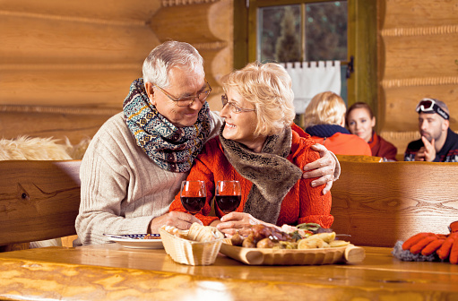 Senior Couple Having Dinner In Restaurant After Skiing Stock Photo - Download Image Now