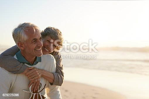 istock Senior couple having fun at the beach 629225096