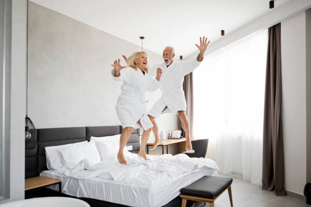 Senior Couple Having Fun in Hotel Room Jumping on a bed – Foto