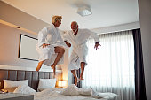 Senior couple jumping on the bed and having fun in hotel room.