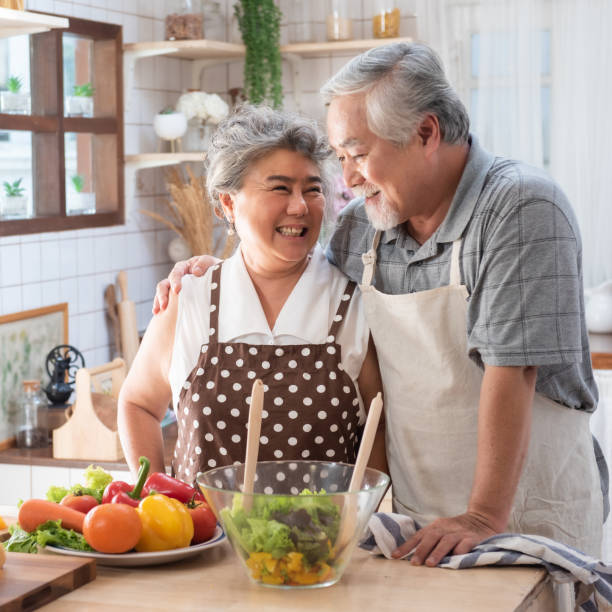 senior couple having fun in kitchen with healthy food - retired people cooking meal at home with man and woman preparing lunch with bio vegetables - happy elderly concept with mature funny pensioner. - vacations food stock pictures, royalty-free photos & images