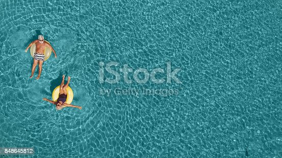 istock Senior couple having fun in the sea 848645812
