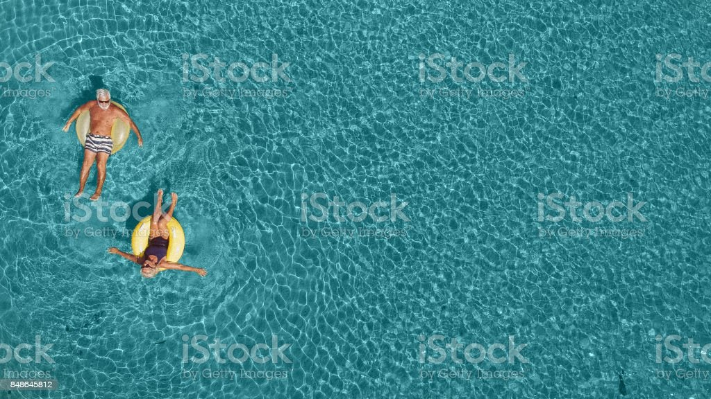 Senior couple having fun in the sea stock photo