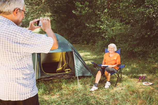 Senior-Paar mit Spaß beim Fotografieren auf dem Campingplatz – Foto
