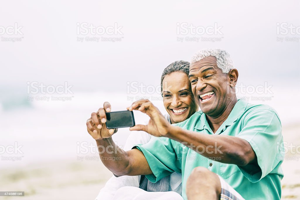 Senior couple s'amuser avec le téléphone intelligent sur la plage - Photo