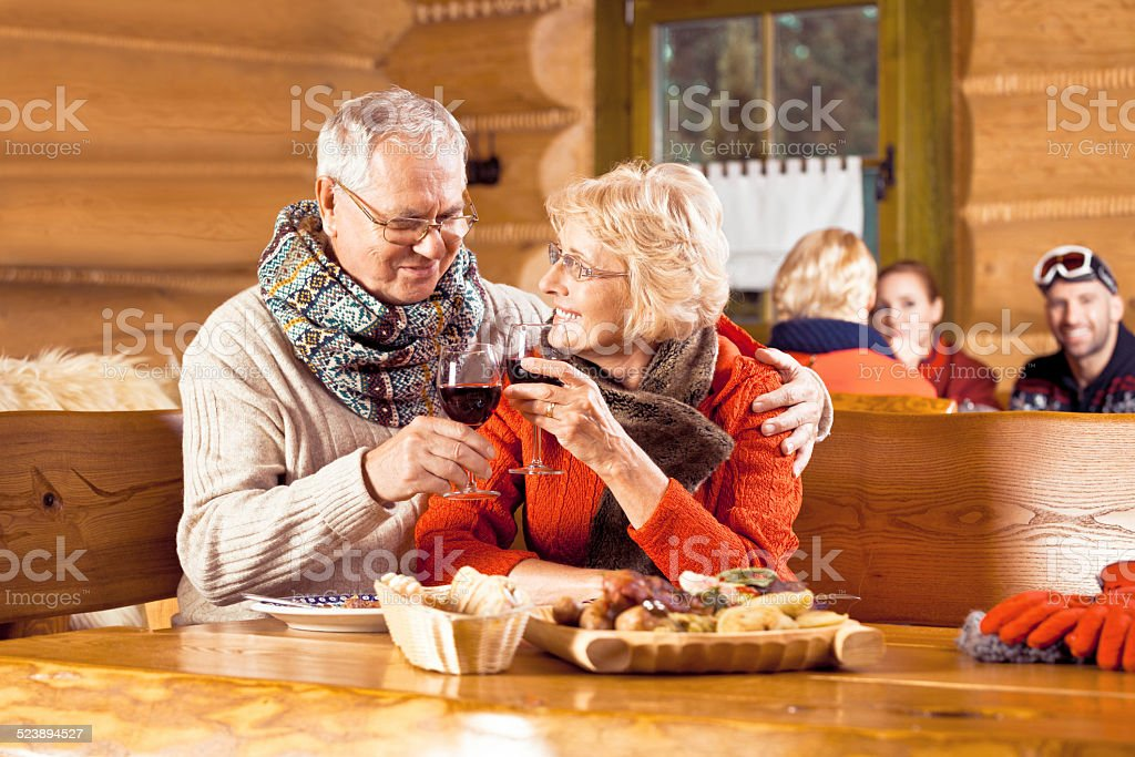 Senior couple having lunch after skiing, toasting wiht wine Senior couple wearing winter clothes sitting in a mountain restaurant after skiing, talking, enjoying dinner and drinking red wine.  60-64 Years Stock Photo
