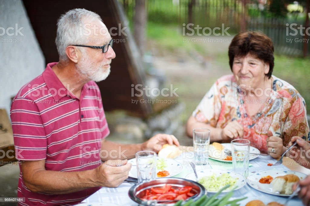 Senior couple having lunch outdoors with friends - Zbiór zdjęć royalty-free (Aktywni seniorzy)