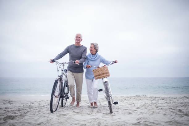 Senior couple having ride with their bike Senior couple having ride with their bike on the beach 65 69 years stock pictures, royalty-free photos & images