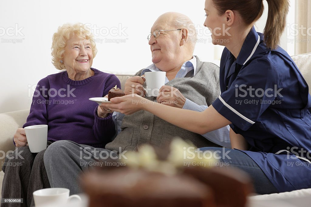 Senior couple having supper with their carer at home royaltyfri bildbanksbilder