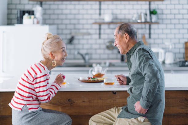 Senior couple having tea in kitchen A senior married couple is having tea in kitchen. only japanese stock pictures, royalty-free photos & images