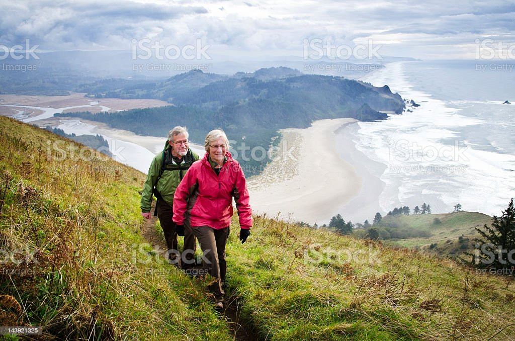 Senior couple hiking above coast stock photo