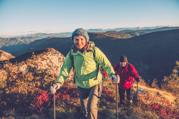 Senior Couple Hiking at Autumnal Dawn in Southern Julian Alps, Europe stock photo