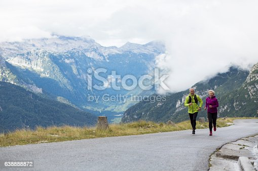 Senior couple running together on road, mountain in background.