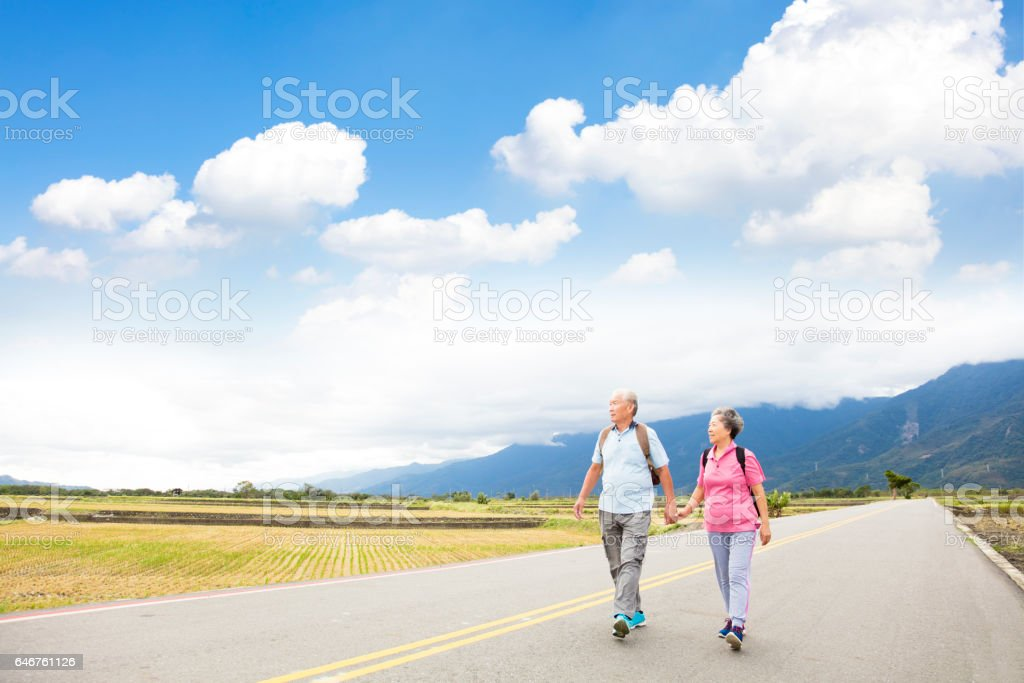 senior couple hiking on the country road stock photo