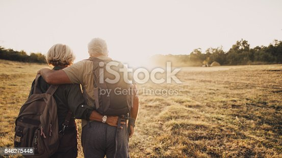 Photo of an elderly couple who still enjoy making memories, searching for new adventures while backpacking; wide photo dimensions