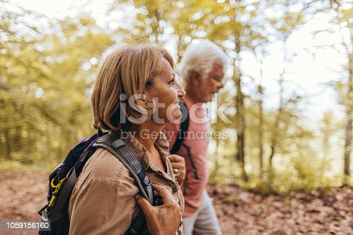 Photo of an elderly couple during their hike with backpacks