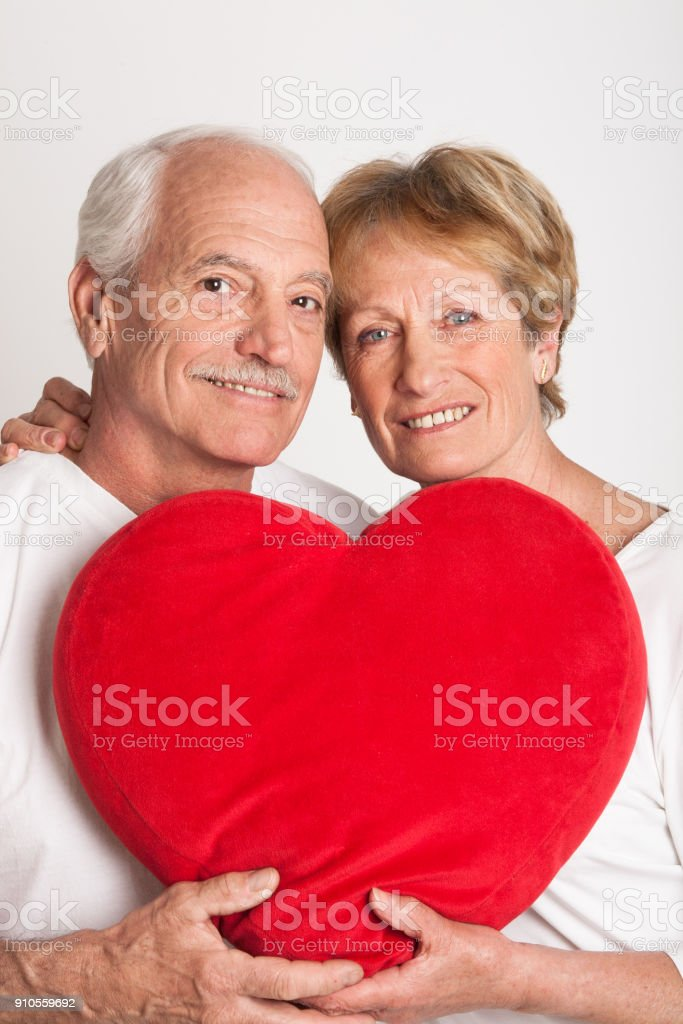 senior couple holding a heart shaped cushion стоковое фото