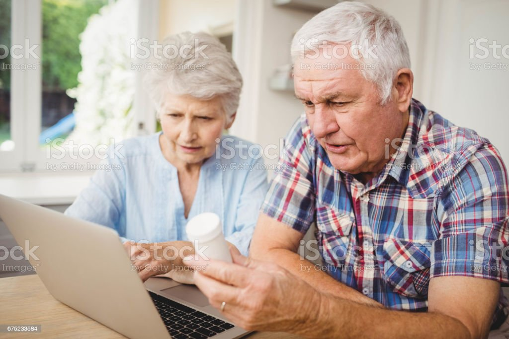 Senior couple holding a pill bottle while operating laptop royalty-free stock photo