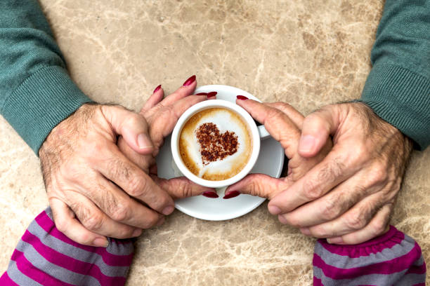senior couple holding hand during morning coffee with heart - senior valentine stock photos and pictures
