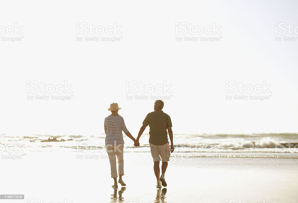 Senior couple holding hands and walking on beach royalty-free stock photo