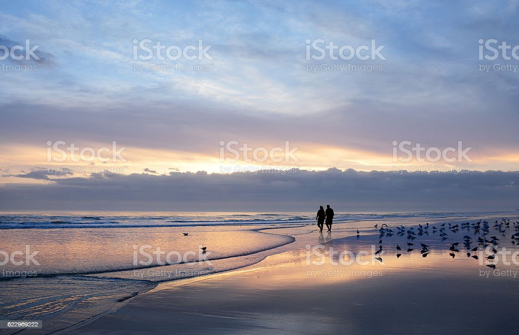 Senior couple holding hands enjoying time on beach at sunrise. stock photo