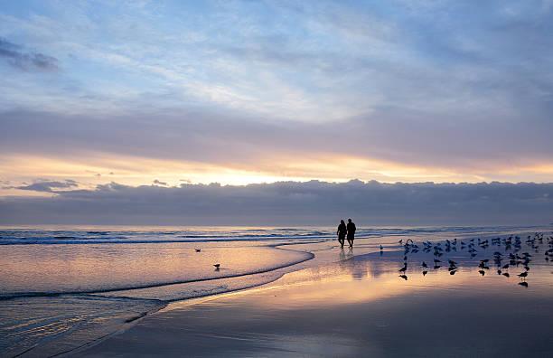Senior couple holding hands enjoying time on beach at sunrise. stock photo