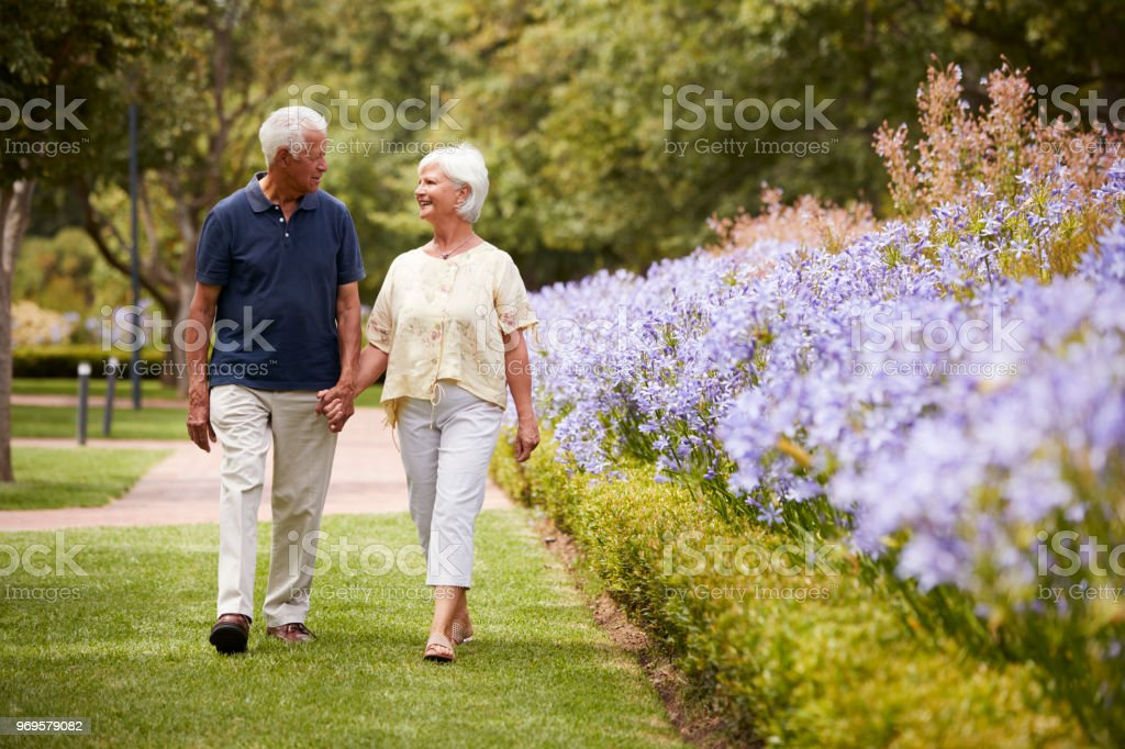 Senior Couple Holding Hands On Romantic Walk In Park Together стоковое фото