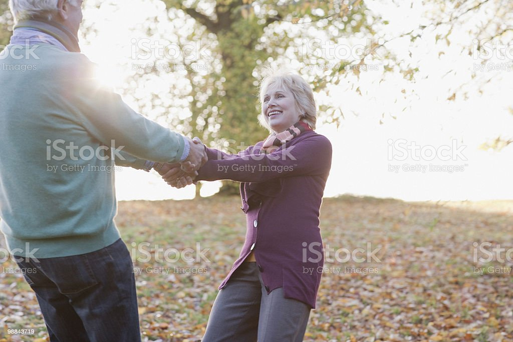 Senior couple holding hands outdoors in autumn royalty-free stock photo