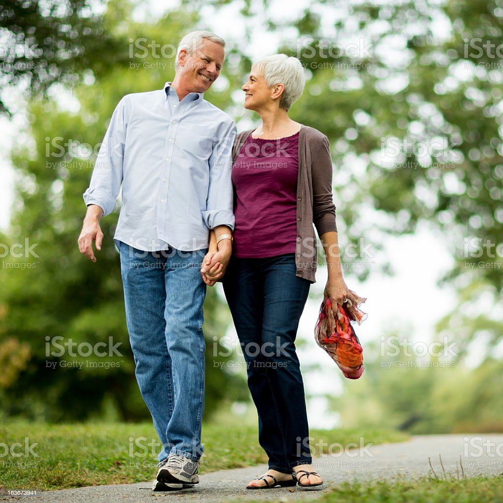 Senior Couple Holding Hands Walking in Park royalty-free stock photo