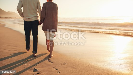 istock Senior couple holding hands walking on the beach 629225214