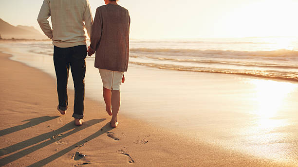 Senior couple holding hands walking on the beach stock photo