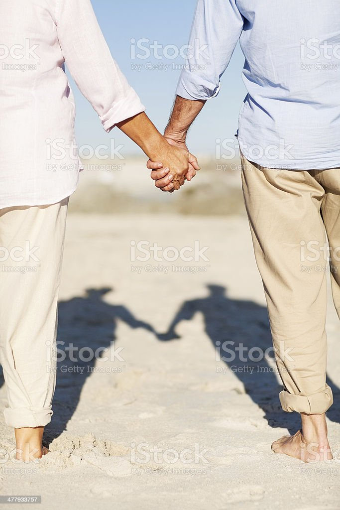 Senior Couple Holding Hands While Standing On Beach royalty-free stock photo