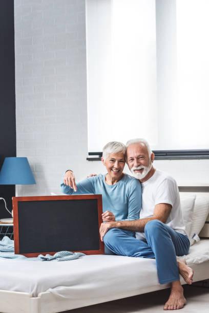 Senior couple holding message board stock photo