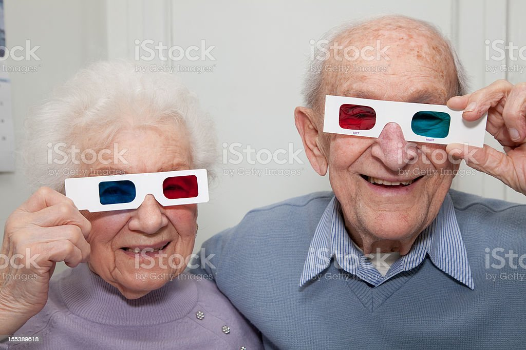 Senior couple holding red- blue 3D glasses stock photo