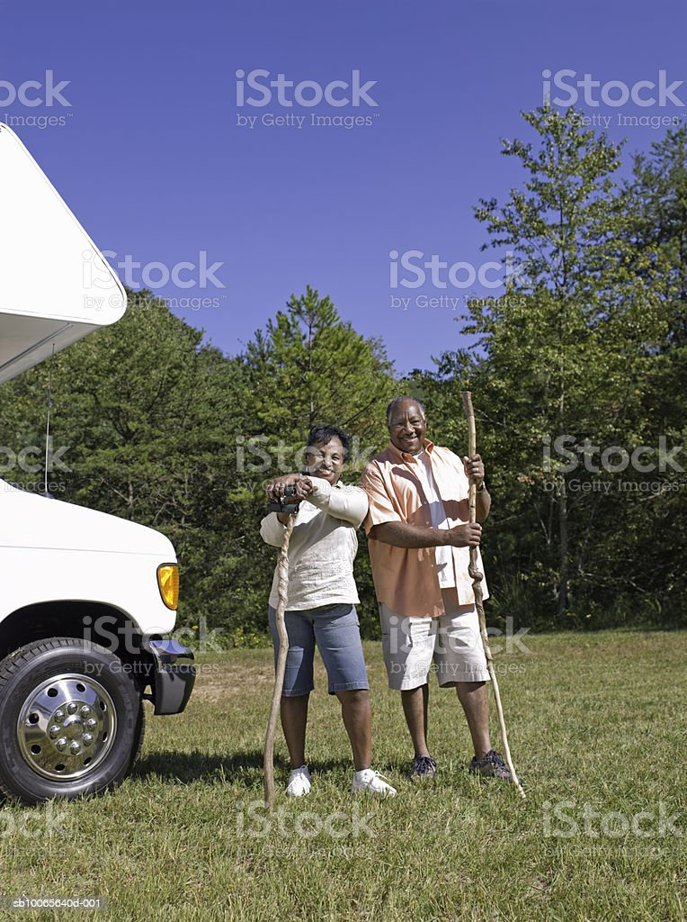 Senior couple holding sticks, standing by motorhome, smiling foto de stock libre de derechos