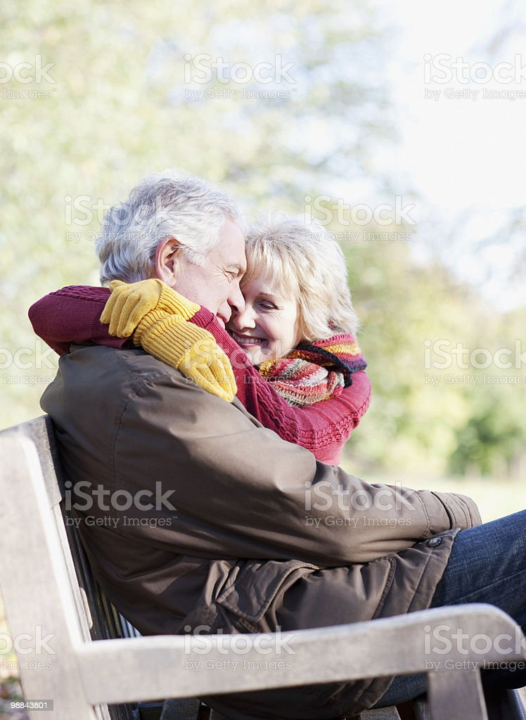 Senior couple hugging in park bench royalty-free stock photo