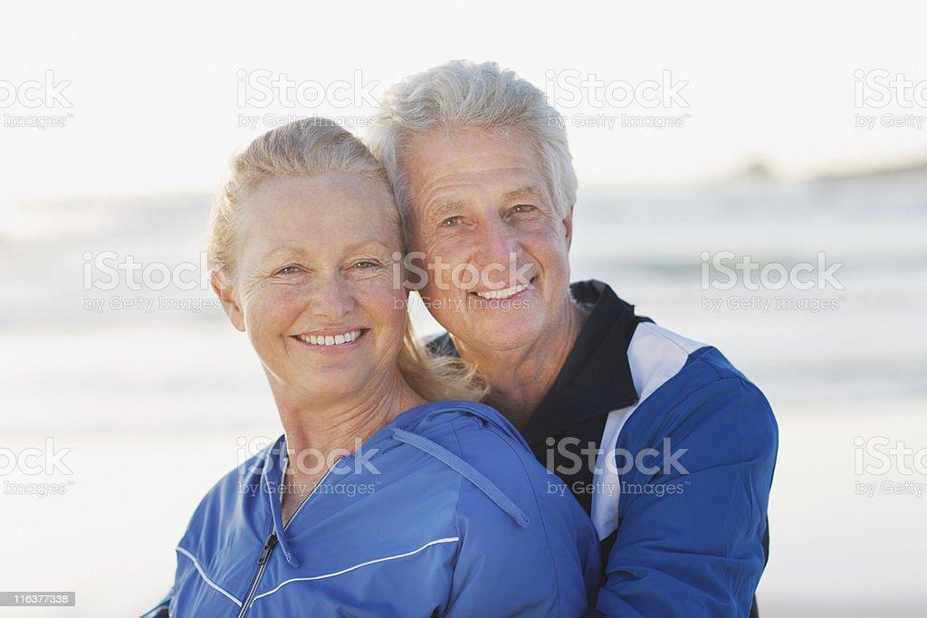 Senior couple hugging on beach stock photo