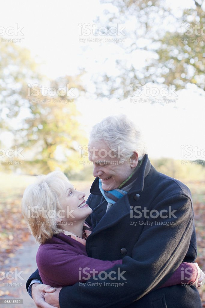 Senior couple hugging outdoors in autumn royalty-free stock photo