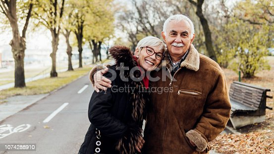 Old couple embracing each other in the park
